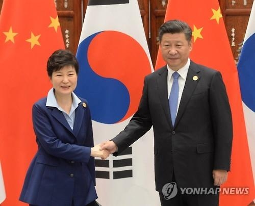 This photo, taken on Sept. 5, 2016, shows President Park Geun-hye (L) shaking hands with Chinese President Xi Jinping before their summit on the sidelines of the gathering of the Group of 20 leading economies in Hangzhou, eastern China. (Yonhap)