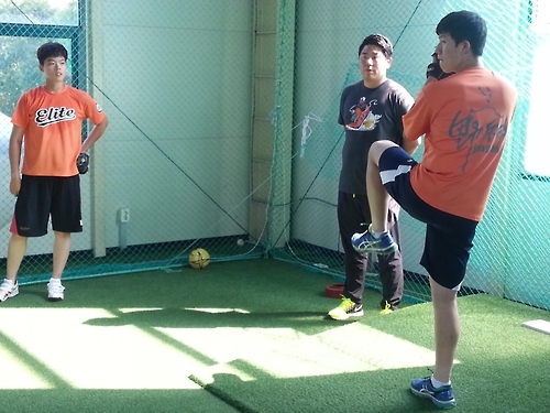 Baseball pitcher Yu Jae-you (R) prepares to make a pitch as his private coach Choi Eun-chul (C) and fellow pitcher Han Seung-ji look on at Choi's Elite Baseball Academy in Incheon on Sept. 5, 2016. (Yonhap)