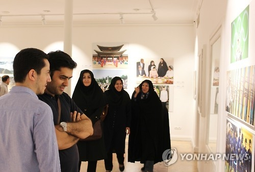 Visitors look at a photo exhibition co-hosted by Yonhap News Agency and IRNA at the Artists House in Tehran on Sept. 27, 2016. (Yonhap)