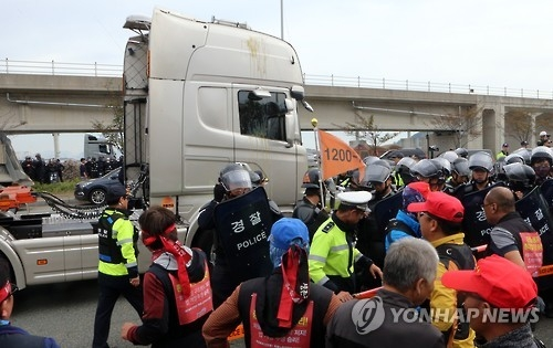 Striking cargo truck drivers throw eggs at a truck of a non-participant in the strike near a seaport in Busan on Oct. 11, 2016. (Yonhap)