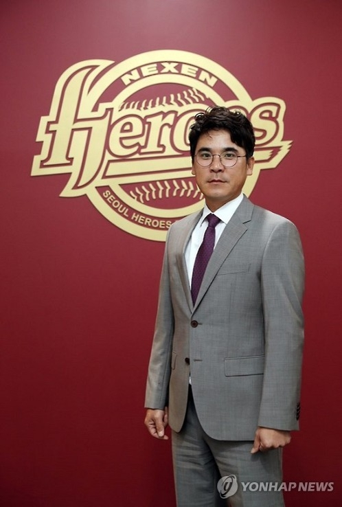 In this undated photo provided by the Nexen Heroes, Jang Jung-suk, the Korea Baseball Organization club's new manager, poses in front of the team's emblem. (Yonhap)