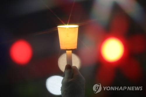 A protester holds up a candle at Gwanghwamun Square in central Seoul on Nov. 26, 2016, while attending a rally calling for President Park Geun-hye's resignation. (Yonhap)