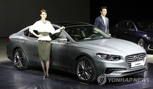The file photo, taken on Nov. 22, 2016, shows a couple of models posing next to the all new Hyundai Grandeur from Hyundai Motor Co. The South Korean automaker unveiled the vehicle as the first of more than 10 new and improved vehicle models to be launched over a one-year period as part of its global marketing strategy. (Yonhap)