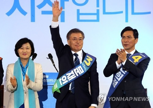 Presidential front-runner Moon Jae-in (C) waves to his supporters after securing his second victory in a party primary held in Daejeon, located some 160 kilometers south of Seoul, on March 29, 2017. His closest rival and South Chungcheong Province Gov. An Hee-jung (R) came in second. (Yonhap)