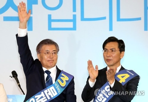 Moon Jae-in (L) of the Democratic Party waves to supporters after winning a primary in the central city of Daejeon on March 29, 2017. South Chungcheong Province Gov. An Hee-jung is seen to his right. (Yonhap)