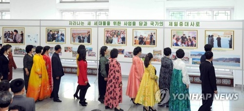 This photo unveiled by North Korea's Central News Agency on April 4, 2017, shows North Koreans seeing photos of leader Kim Jong-un's feats at an exhibition held in Pyongyang to mark the fifth anniversary of him being elected to the top posts of the country. (For Use Only in the Republic of Korea. No Redistribution) (Yonhap)