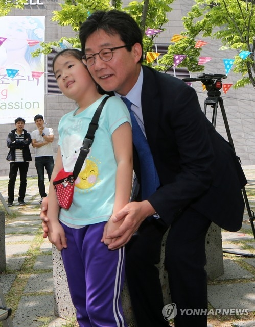 Yoo Seong-min, the presidential candidate of the splinter conservative Bareun Party, poses for a photo with a girl on the campaign trail in the southeastern port city of Busan on April 30, 2017. (Yonhap)