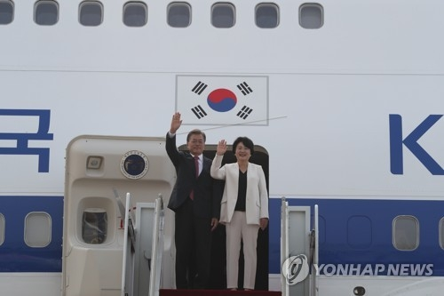 South Korean President Moon Jae-in and his wife Kim Jung-sook wave before boarding Air Force One bound for Germany at Seoul's Seongnam Airport on July 5, 2017. (Yonhap)