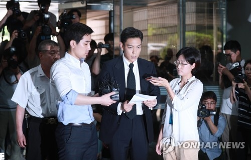 Surrounded by reporters, rapper T.O.P. of popular South Korean boyband BIGBANG reads out an apology note on his way to the courthouse to stand trial on charges of smoking marijuana in Seoul on June 29, 2017. (Yonhap)
