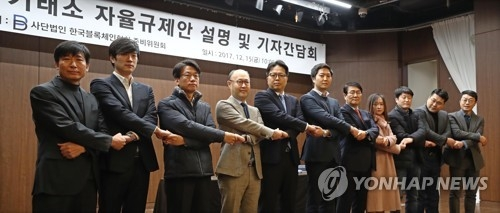 Representatives of South Korean cryptocurrency exchanges hold each other's hands after announcing a set of self-regulatory measures aimed at improving transparency of trade during a press briefing in Seoul on Dec. 15, 2017. (Yonhap)