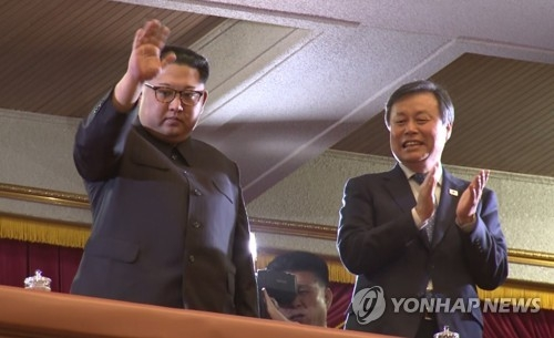 North Korean leader Kim Jong-un (L) waves at the crowd during a performance by a South Korean art troupe at East Pyongyang Grand Theatre in Pyongyang, in this photo captured from a pool report video on April 1, 2018, while South Korea's cultural minister, Do Jong-whan, applauds at his side. (Yonhap)