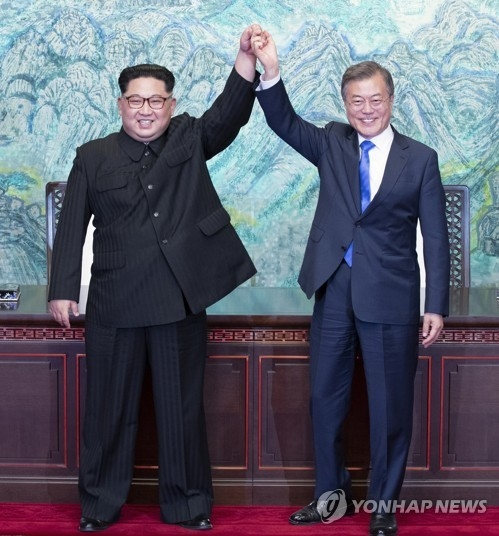 South Korean President Moon Jae-in (R) and North Korean leader Kim Jong-un raise their hands after signing a joint declaration on the southern side of the truce village of Panmunjom on April 27, 2018. (Yonhap)