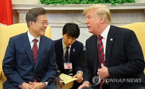 In the photo, taken May 22, 2018 (U.S. time), South Korean President Moon Jae-in (L) and U.S. President Donald Trump are seen talking to each other in a bilateral summit held at the White House. (Yonhap)
