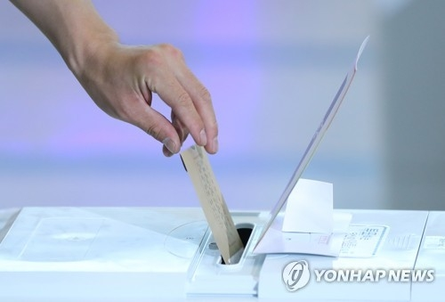 This photo, taken June 8, 2018, shows a voter casting a ballot at a polling center set up at Seoul Station on the first day of early voting for the June 13 local elections and parliamentary by-elections. (Yonhap)