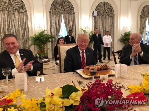 This photo, captured from Singaporean Foreign Minister Vivian Balakrishnan's Facebook page, shows U.S. President Donald Trump (C) flanked by U.S. Secretary of State Mike Pompeo (L) and Chief of Staff John Kelly at the Istana palace in Singapore on June 11, 2018. (Yonhap)