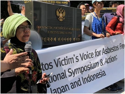 This photo provided by the Citizen's Center for Environment and Health shows an Indonesian anti-asbestos activist and South Korean activists rallying in front of the Russian Embassy in Seoul on July 3, 2018. (Yonhap)