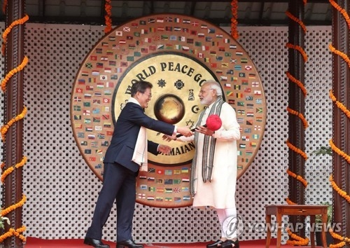 South Korean President Moon Jae-in (L) shakes hands with India's Prime Minister Narendra Modi (R) after hitting the World Peace Gong at Gandhi Museum in New Delhi on July 9, 2018. (Yonhap)
