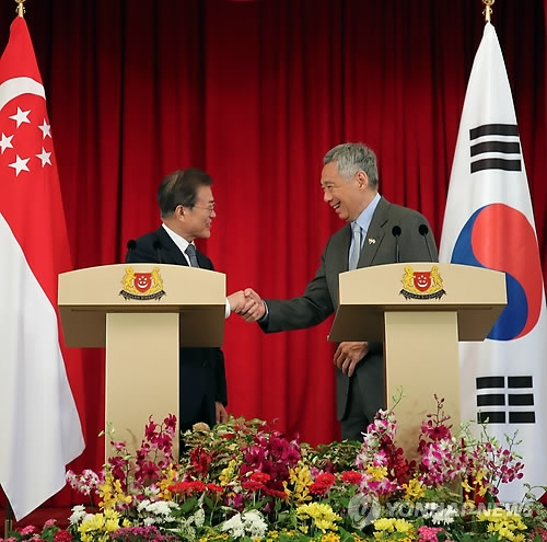 South Korean President Moon Jae-in (L) and Singaporean Prime Minister Lee Hsien Loong shake hands after a joint press conference that followed their bilateral summit in Singapore on July 12, 2018. (Yonhap)