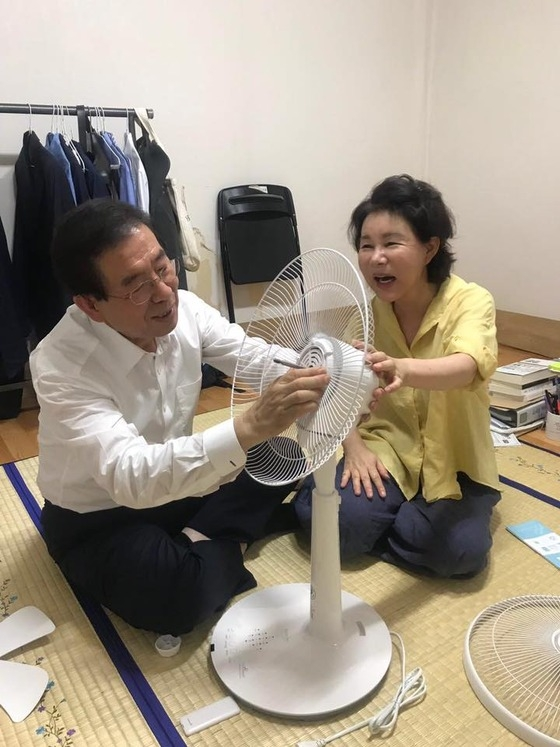 This photo captured from Seoul Mayor Park Won-soon's Facebook page shows Park and his wife assembling an electric fan from President Moon Jae-in at his temporary rooftop home in Samyang-dong, northern Seoul, on July 27, 2018. (Yonhap)
