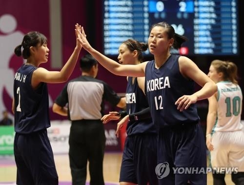 Park Ji-hyun of South Korea (L) and Ro Su-yong of North Korea, teammates on the unified Korean women's basketball team, high-five each other during a Group X match against Kazakhstan at the 18th Asian Games at GBK Basketball Hall in Jakarta on Aug. 21, 2018. (Yonhap)