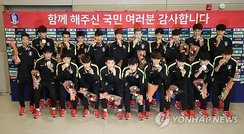In this file photo from Sept. 3, 2018, players on the South Korean men's football team at the Jakarta-Palembang Asian Games bite their gold medals after landing at Incheon International Airport, west of Seoul. The Korean-language sign behind them thanks the fans for their support. (Yonhap)