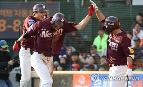 Lim Byeong-wuk of the Nexen Heroes (C) high-fives teammate Kim Min-sung (R) after hitting a three-run homer against the Hanwha Eagles in the top of the fifth inning of Game 2 of the first round series in the Korea Baseball Organization postseason at Hanwha Life Eagles Park in Daejeon, 160 kilometers south of Seoul, on Oct. 20, 2018. (Yonhap)