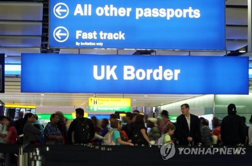 This undated file photo shows visitors forming a long line at Heathrow airport's immigration gate in London. (Yonhap)