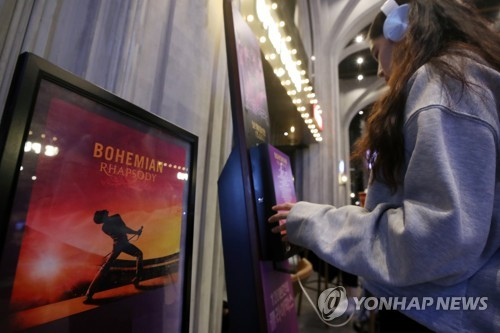 "A moviegoer listens to the soundtrack of the musical film sensation ""Bohemian Rhapsody"" at a Seoul theater on Dec. 3, 2018. A day earlier, the film crossed the 6 million mark in the number of cumulative admissions since its release in the country on Oct. 31. (Yonhap)"