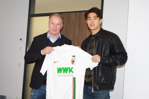 In this photo provided by Incheon United football club on Dec. 13, 2018, Cheon Seong-hun (R), a forward on Incheon's under-18 team, holds up a uniform for FC Augsburg, after signing a 4.5-year deal with the Bundesliga club. (Yonhap)