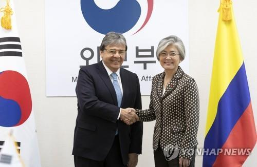 South Korean Foreign Minister Kang Kyung-wha (R) shakes hands with her Colombian counterpart Carlos Holmes Trujillo García during a meeting in Seoul on Dec. 17, 2018. (Yonhap)