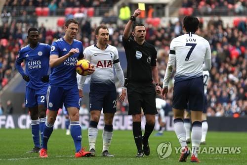 In this AFP photo, referee Michael Oliver (2nd from R) shows a yellow card to Tottenham Hotspur's South Korean forward Son Heung-min during the English Premier League football match between Tottenham Hotspur and Leicester City at Wembley Stadium in London on February 10, 2019. (Yonhap)