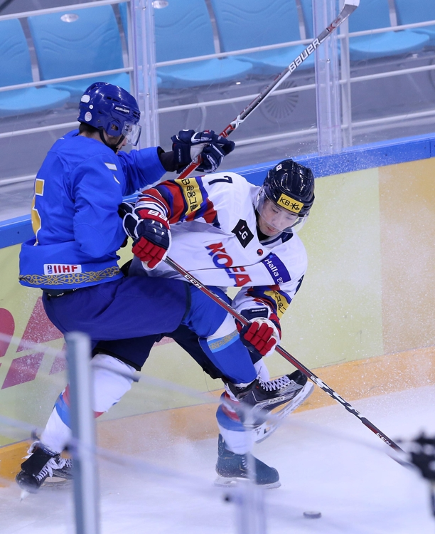 In this photo provided by the Korea Ice Hockey Association on Feb. 7, 2019, Park Sang-jin of South Korea (R) battles Dmitriy Bykov of Kazakhstan during their match at the Legacy Cup men's hockey tournament at Gangneung Hockey Centre in Gangneung, 230 kilometers east of Seoul. (Yonhap)