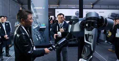 This photo, provided by Naver LABS, shows CEO Seok Sang-ok (C) showcasing the company's AMBIDEX at this year's Consumer Electronics Show (CES) in Las Vegas. (Yonhap)