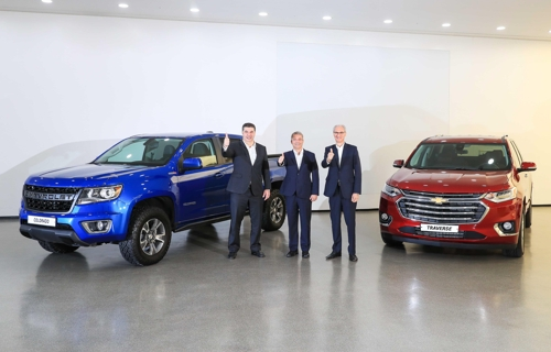 In this photo provided by GM Korea, GM Korea President and CEO Kaher Kazem (L), GM International President Julian Blissett (C) and GM Technical Center Korea President Roberto Rempel hold up their thumbs before a press event at the GM design center in Incheon on June 25, 2019. (PHOTO NOT FOR SALE) (Yonhap)