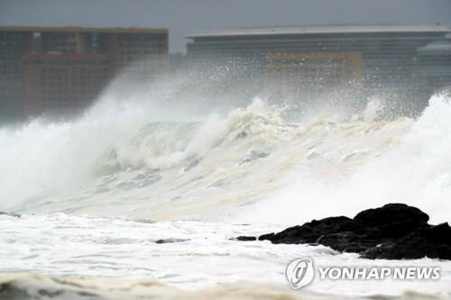 A towering wave crashes onto the southern resort island of Jeju on July 19, 2019, as Typhoon Danas approaches. (Yonhap)