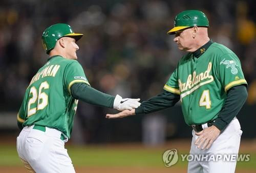 In this Getty Images file photo from May 10, 2019, Matt Williams (R), third base coach of the Oakland Athletics, congratulates Matt Chapman after Chapman's walk-off solo home run against the Cleveland Indians in the bottom of the 12th inning of a Major League Baseball regular season game at Oakland Coliseum in Oakland, California. (Yonhap)