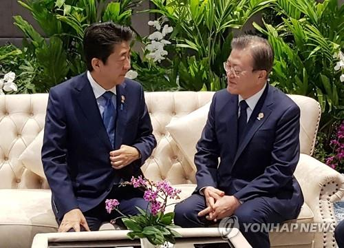South Korean President Moon Jae-in (R) talks with Japanese Prime Minister Shinzo Abe ahead of the 22nd ASEAN Plus Three summit in Bangkok on Nov. 4, 2019, in this photo provided by Cheong Wa Dae. (PHOTO NOT FOR SALE) (Yonhap)