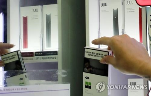 An employee of GS25 clears e-cigarettes from shelves in a Seoul store on Oct. 24, 2019, after the convenience store chain decided to suspend sales of the vaping products over health concerns. (Yonhap)
