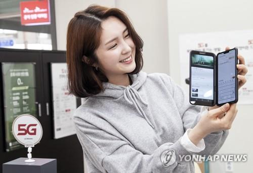 In this photo provided by SK Telecom Co., a model shows an LG V50 ThinQ with a second screen that goes on sale in South Korea on May 10, 2019.