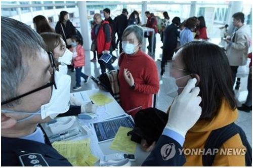 A quarantine official (L) checks a traveller for fever and other symptoms at South Korea's Incheon International Airport, west of Seoul, in this file photo taken on Jan. 20, 2020. (Yonhap)