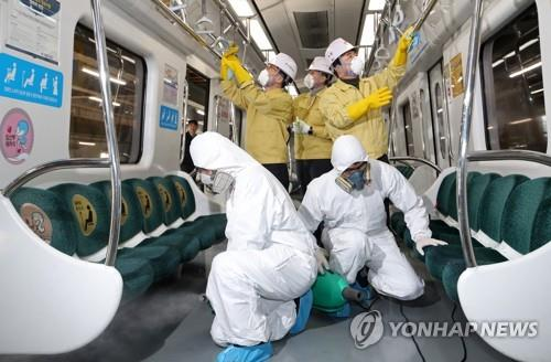 Subway workers in Gwangju 330 kiloemters south of Seoul disinfect a passenger car on Feb. 4, 2020, amid concerns the novel coronavirus may have spread in the city. (Yonhap)