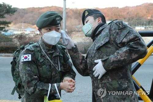A soldier has her temperature taken by a sentry at the gate of an Army unit in the town of Goyang, near Seoul, on Feb. 4, 2020, as part of measures to prevent the spread of the new coronavirus that has broken out in China. (Yonhap)