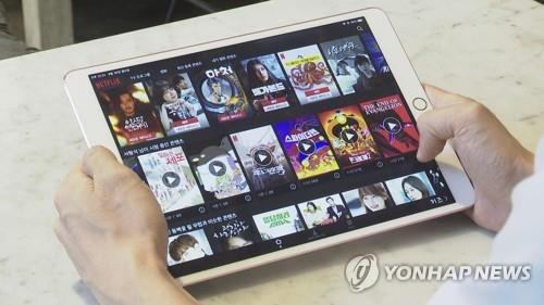 This undated image from Yonhap News TV shows a person browsing an over-the-top (OTT) platform on a tablet. (PHOTO NOT FOR SALE) (Yonhap)