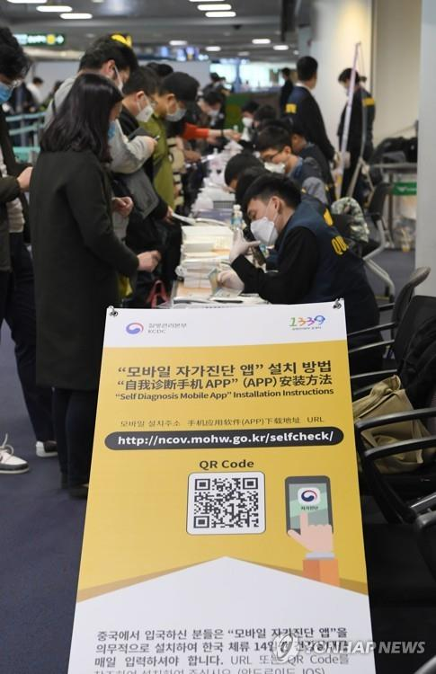 Tourists from China, Hong Kong and Macao install an application on their smartphones that the health ministry has released to help people check if they have coronavirus, dubbed COVID-19, with the help of airport officials at the arrival gate of Incheon International Airport, west of Seoul, on Feb. 13, 2020. (Pool photo) (Yonhap)