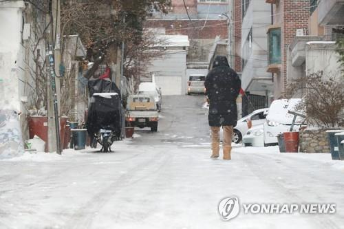 A citizen walks carefully on a snow-covered road in western Seoul on Feb. 17, 2020. (Yonhap)
