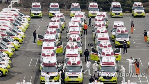 Ambulances are parked outside a water purification plant in Daegu on March 1, 2020, with emergency workers checking their vehicles. (Yonhap)