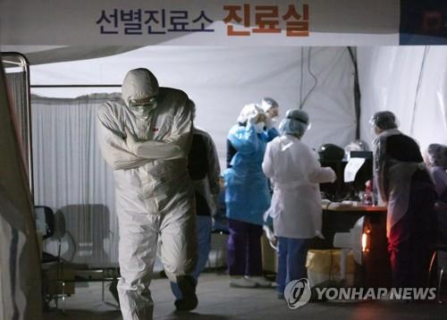 A medical worker shivers in the cold at a special facility set up to treat coronavirus patients at a public hospital in Seoul on March 4, 2020. (Yonhap)