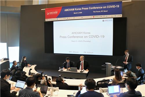 This photo taken on March 5, 2020, and provided by the American Chamber of Commerce in Korea (AMCHAM) shows AMCHAM Chairman & CEO James Kim (L) and Jeffrey Jones, chairman of the AMCHAM Board of Governors, delivering a briefing on AMCHAM member firms' stance toward the South Korean government's reaction to the spreading coronavirus outbreak at a press conference at the International Finance Corporation mall in Yeouido, Seoul. (PHOTO NOT FOR SALE) (Yonhap)