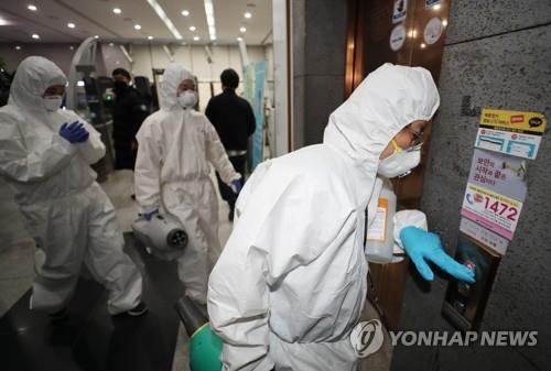 Health officials enter the government complex in Sejong on March 7, 2020, to disinfect an office after a public servant was diagnosed with the COVID-19 virus. (Yonhap)