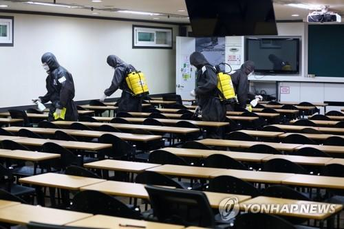 Quarantine officials carry out a disinfection operation against the new coronavirus at a cram school in Daegu, 302 kilometers south of Seoul, on March 15, 2020. (Yonhap)
